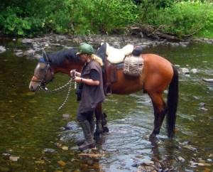 Kobold und Reiterin zu Fuß im Wasser
